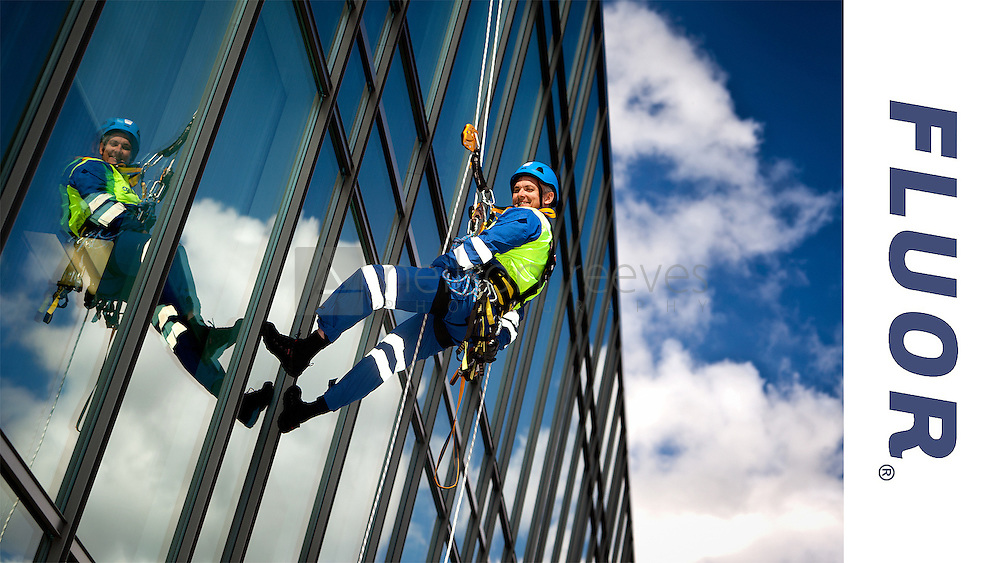advertising photograph of professional abseiler, abseiling down the side of glass building with beautiful blue sky above and the abseiler is reflected in the building