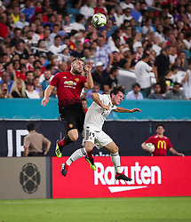 July 31, 2018 - Miami Gardens, Florida, USA - Manchester United F.C. defender Luke Shaw (23) leaps to head the ball above Real Madrid C.F. defender Alvaro Odriozola (19) during an International Champions Cup match between Real Madrid C.F. and Manchester United F.C. at the Hard Rock Stadium in Miami Gardens, Florida. Manchester United F.C. won the game 2-1. (Credit Image: © Mario Houben via ZUMA Wire)
