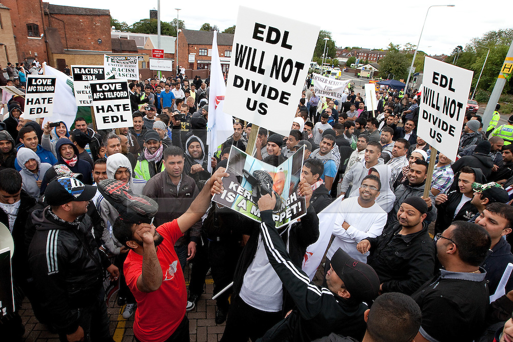 © Licensed to London News Pictures. 13/08/2011. Telford, UK. A demonstration to oppose the EDL in Wellington. Demonstraters use shoes to smash a picture of prominent EDL member, Guramit Singh. The EDL demonstrate against a paedophile ring in the small Telford town of Wellington. The group were going to march, however the Home Secretary imposed a ban on all marches in the area. About 300 EDL supporters attended. The EDL demonstration was counter-protested by about 300 people. Photo credit : Joel Goodman/LNP