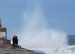 © Licensed to London News Pictures. <br /> 01/02/2015. <br /> <br /> South Gare, Redcar, United Kingdom<br /> <br /> Two people stand and watch waves crash against the sea wall at the mouth of the Tees at South Gare near Redcar in Teesside.<br /> <br /> Photo credit : Ian Forsyth/LNP