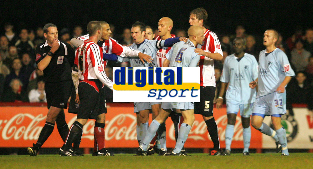 Photo: Frances Leader.<br />Brentford v Chesterfield. Coca Cola League 1. <br />10/12/2005.<br />Brentfords' captain Ricky Newman (3rd, R) and Chesterfield's Derek Niven get a yellow card each for having a disagreement and are separated by team mates.