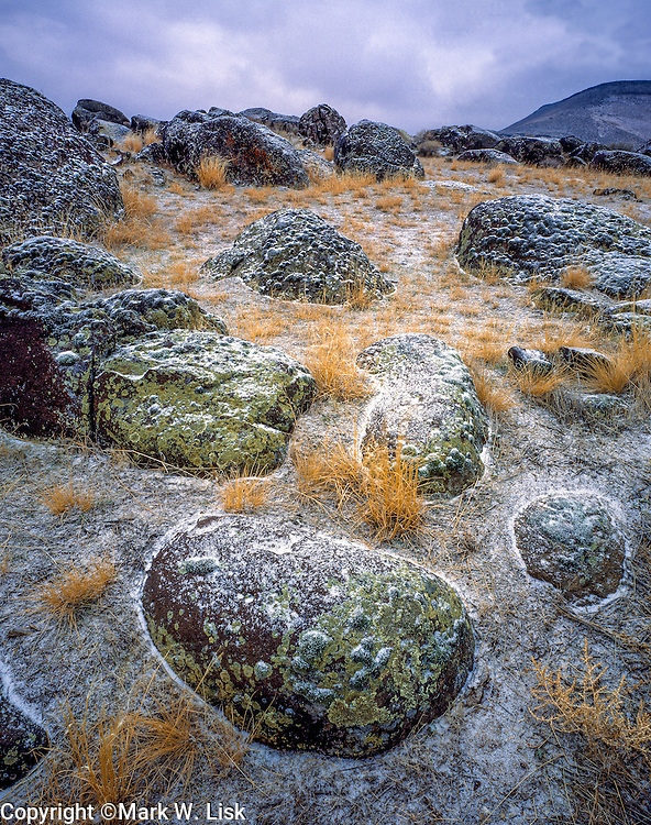 Snow dust round basalt rocks on the desolate River Plain in the Snake river Birds of prey area.