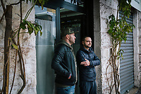 TARANTO, ITALY - 22 FEBRUARY 2018: (L-R) Alessio Peretto (42), who has worked at the ILVA steel mill since 200  but is nonetheless part of activist group trying to shut it down, and Luca Greco, a 30 years-old unemployed man living with his parents in Tamburi, the working-class district adjacent ILVA, chat at the Mini Bar in Taranto, Italy, on February 22nd 2018.<br /> <br /> Taranto, a  formerly lovely town on the Ionian Sea has for the last several decades been dominated by the ILVA steel mill, the largest steel plant in Europe. It was built by the government in the 1960s as a means of delivering jobs to the economically depressed south, but has been implicated for a cancer as dioxin and mercury have seeped into local groundwater, tainting the food supply, while poisoning the bay and its once-lucrative mussels.