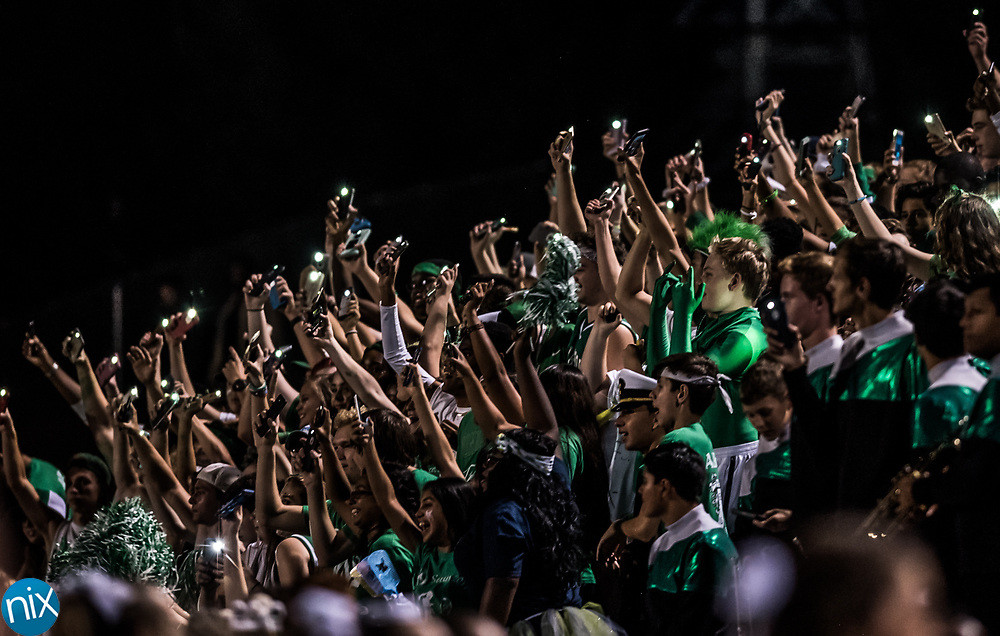 Kannapolis fans hold up cell phone lights after one of the stadium lights went out causing a delay during the annual Battle for the Bell game. Kannapolis won 14-12.