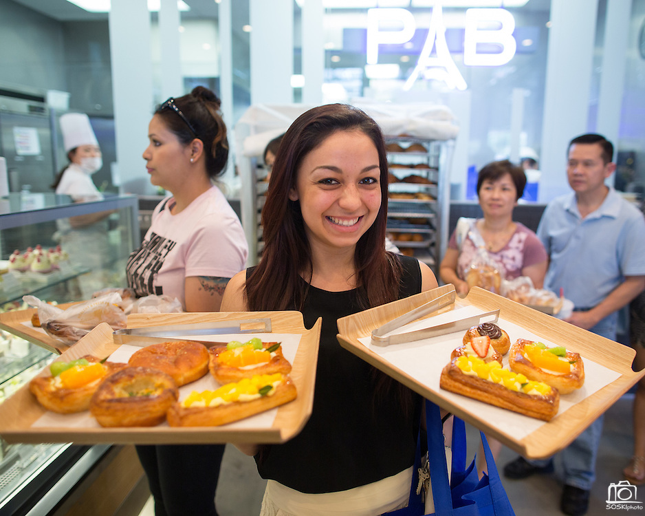 Sofia Varela of San Francisco poses for a portrait with two platters of pastries during the Grand Opening Ribbon Cutting Ceremony at Paris Baguette Cafe in Milpitas, California, on May 16, 2014. (Stan Olszewski/SOSKIphoto)