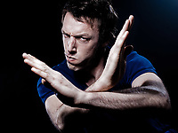 studio portrait on black background of a funny expressive caucasian man anger refuse gesture
