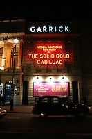 taxis pass garrick theatre in london's west end
