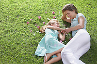 Mother and daughter (5-6) lying on lawn with flowers strewn nearby
