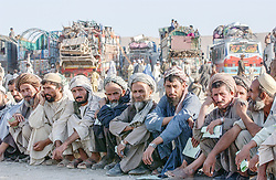 Afghan refugees  returning from Iran stop in a transit camp set up by the United Nations High Commission for Refugees on the edge of Kabul, Afghanistan where they recieve medical and monetary assistance   before they return home  August 10, 2002. Children were being vaccinated for measels and adults were given $10 to complete their long journey home. (photo by Ami Vitale)