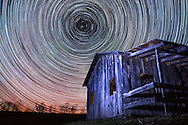 Star trails encircling an abandoned wooden shack at Calhoun County Park in West Virginia.