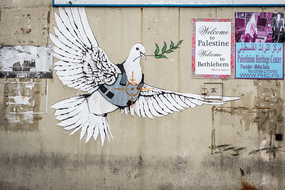 "Located on a building in Bethlehem, this piece of urban art is accredited to Banksy and perhaps several other street artists. The dove, complete with an armored vest and bull's-eye heart target, makes a tongue-in-cheek comment about peace. What better way to display a political comment about the unstable peace in the area than to depict the bearer of peace""the dove""in a precarious situation?"
