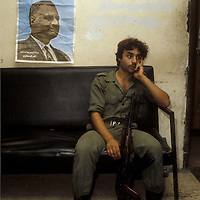 A militia soldier loyal to Gamal Abdel Nasser sits at his guard post in Beirut, Lebanon under a worn poster of Nasser in the wake of the assassinaiton of Anwar Sadat in 1981.