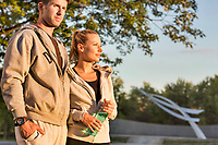 Man embracing her girlfriend after work out in park with lens flare