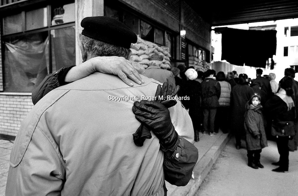 A husband and wife greet each other after four years of separation, on the Serb-side of the Bratstvo i Jedinstvo Most (Brotherhood and Unity bridge) during the final days of the siege of the city, Sarajevo, Bosnia and Herzegovina, February 1996. PHOTO BY ROGER RICHARDS