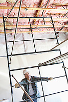 Construction worker looking up at incomplete ceiling
