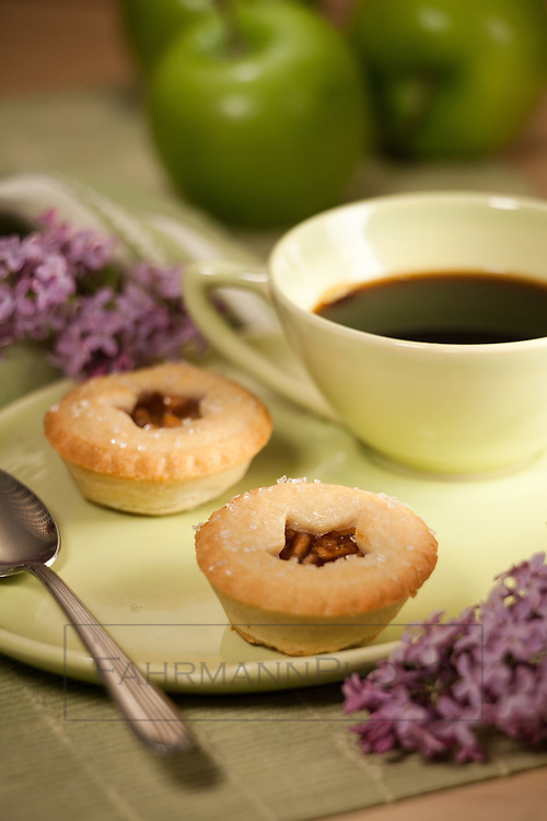 Two bite-sized apple pies sit atop a 60's cup and saucer.