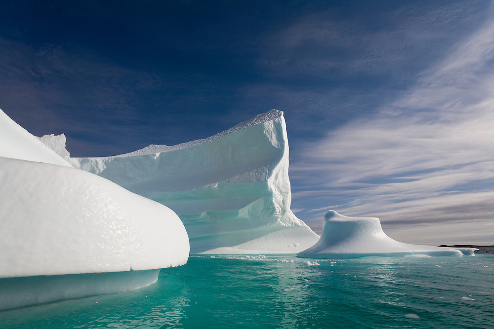 Greenland, Alluitsup Paa (Sydproven), Massive iceberg floats along southwestern coastline on summer afternoon