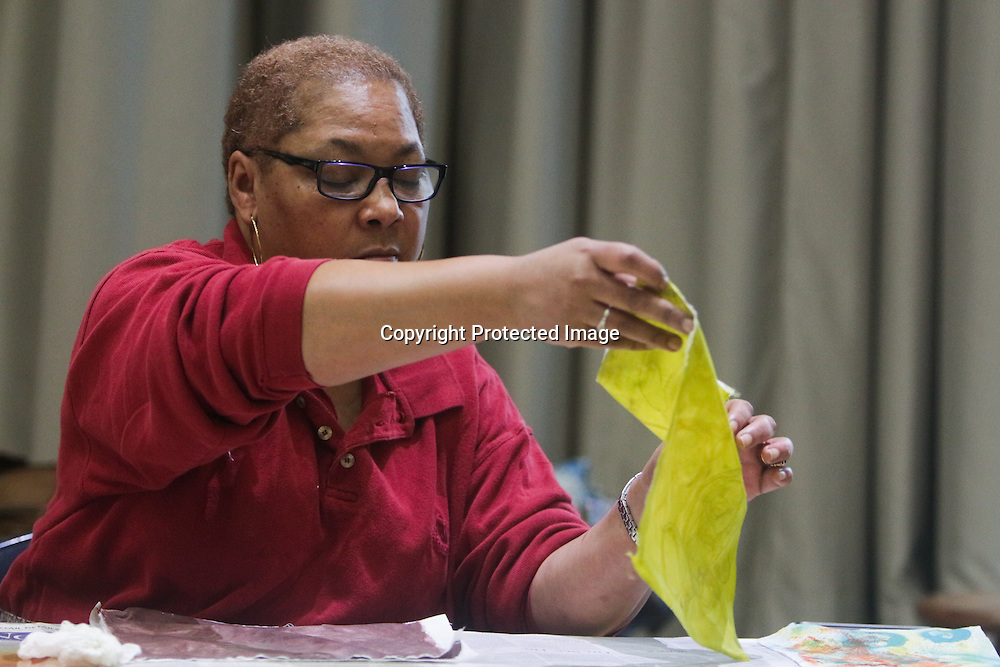 """Althea Johnson straightens a quilt square during """"Create Your Own Quilt Squares"""" Sunday November 23, 2014 at the Cameron Art Museum in Wilmington, N.C. (Jason A. Frizzelle)"""