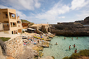 Cala de S'Amunia. Local youngsters swimming and sunbathing.
