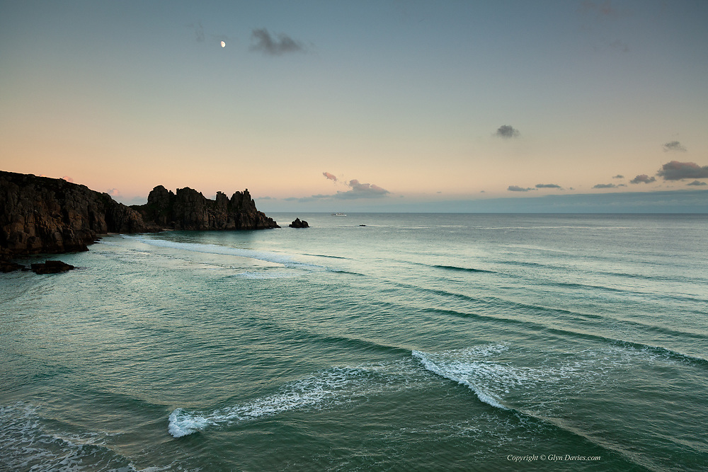 A moon hovers overhead as the Isles of Scilly ferry, the Scillonian, sails past Logan Rock and Treen Cliff near Porthcurno at dusk from St Marys.