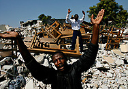 Chery Cherubin, 41, front, and Dorvilier Gismane,  31, raise their hands to God during a service at the Haitian Ministry Theophile Church in Christ in Matissant, a neighborhood in Port-au-Prince, during a national day of mourning, on the one month anniversary of the earthquake that rocked Haiti. The rubble they're standing in is from part of the church, with the pews piled up.