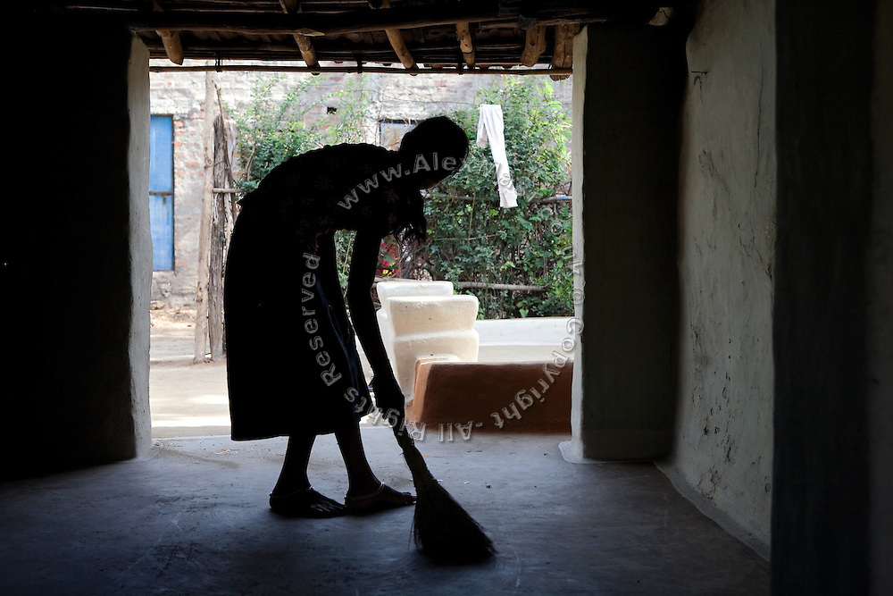 Pooja, 14, a student from the village of Pathpuri, Hoshangabad, Madhya Pradesh, India, taking part to the children's journal, a project launched by Dalit Sangh, an NGO which has been working for the uplift of scheduled castes for the past 22 years, is sweeping her home's floor. Dalit Sangh is working in collaboration with Unicef India to promote education and awareness within backward communities. .