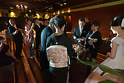 guests photographing cutting of the cake at a western style wedding party Japan