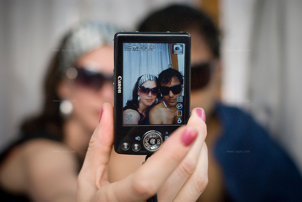 An Indian guy and an american woman take  a picture of themselves together at the Aqua pool club of the Park Hotel in New Delhi.