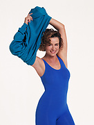 Happy woman in blue exercise leotard and tights in front of white background removing her sweatshirt above her head