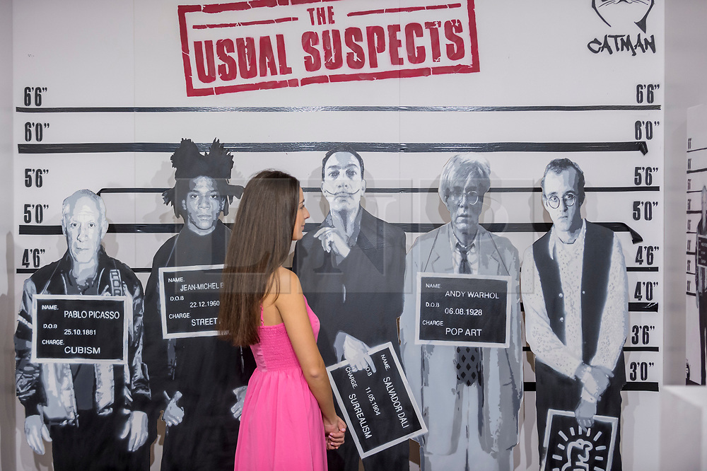 """© Licensed to London News Pictures. 04/10/2018. LONDON, UK. A staff member views """"The Usual Suspects"""" by Catman, an artwork comprising mugshots of major contemporary artists.  Preview of Moniker Art Fair, taking place during Frieze Week at the Old Truman Brewery, near Brick Lane.  Now in its tenth year, the fair embraces contemporary urban art from emerging and established artists  This year, the show's theme is 'Uncensored', shedding light on social, economic and ecological issues, and is open 4 to 7 October.  Photo credit: Stephen Chung/LNP"""
