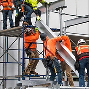Scaffolding workers assemblings scaffolding passageway around the outside of building.<br />