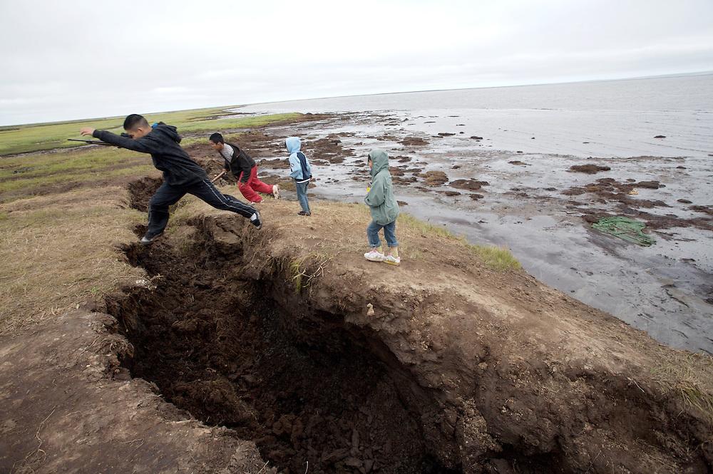 Children in Newtok, Alaska playing on land erosion. 2008