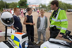 Three boys talking to a Community Policeman at the WOMAD (World of Music; Arts and Dance) Festival in reading; 2005,