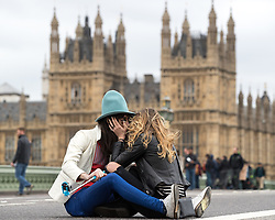 © Licensed to London News Pictures . 29/03/2017 . London , UK . A couple sit on a closed Westminster Bridge and kiss and pose for selfies , ahead of a memorial event on Westminster Bridge , commemorating the lives of those killed in Khalid Masood's terrorist attack in Westminster that took place on 22nd March 2017 (one week ago) . Photo credit: Joel Goodman/LNP