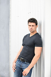 handsome man in a tee shirt leaning against a wall