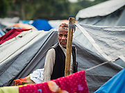 05 AUGUST 2015 - KATHMANDU, NEPAL: A man walks through a large Internal Displaced Person (IDP) Camp in the center of Kathmandu. The camp is next to one the most expensive international hotels in Kathmandu. More than 7,100 people displaced by the Nepal earthquake in April live in 1,800 tents spread across the space of three football fields. There is no electricity in the camp. International NGOs provide water and dug latrines on the edge of the camp but the domestic waste water, from people doing laundry or dishes, runs between the tents. Most of the ground in the camp is muddy from the running water and frequent rain. Most of the camp's residents come from the mountains in northern Nepal, 8 - 12 hours from Kathmandu. The residents don't get rations or food assistance so every day many of them walk the streets of Kathmandu looking for day work.    PHOTO BY JACK KURTZ