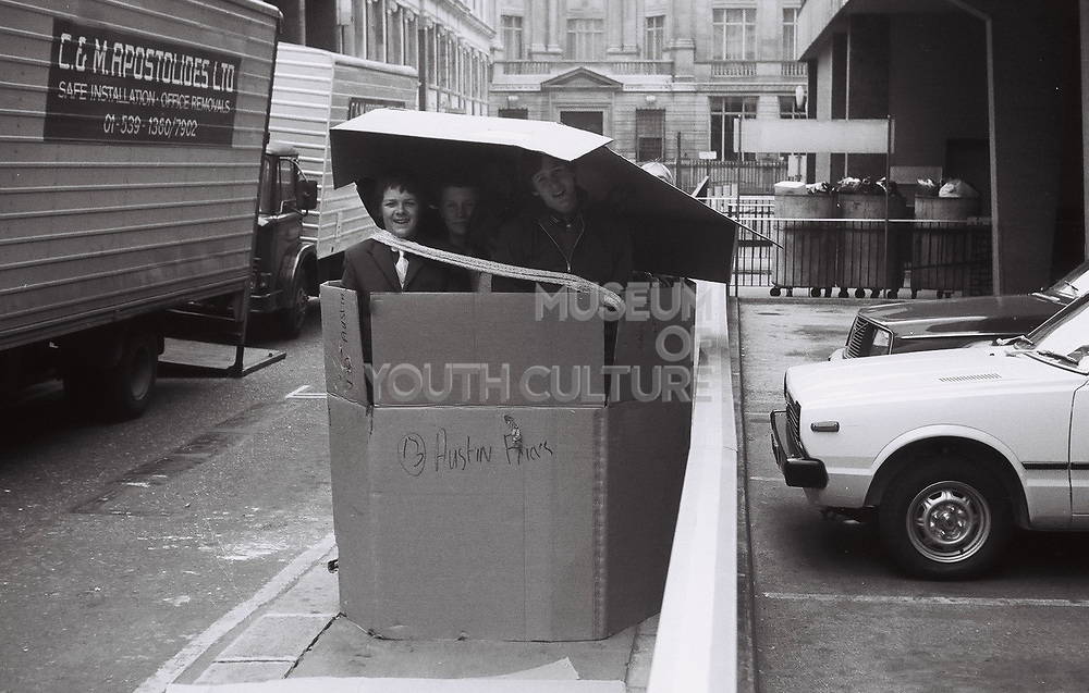 Three teenage friends in a cardboard box somewhere in the city of London.  London, UK, 1980s.