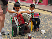 """Two boys prepare accordions to busk in a street fair in San Telmo (""""Saint Pedro González Telmo""""), the oldest historic neighborhood (barrio) in the heart of Buenos Aires, Argentina, South America."""