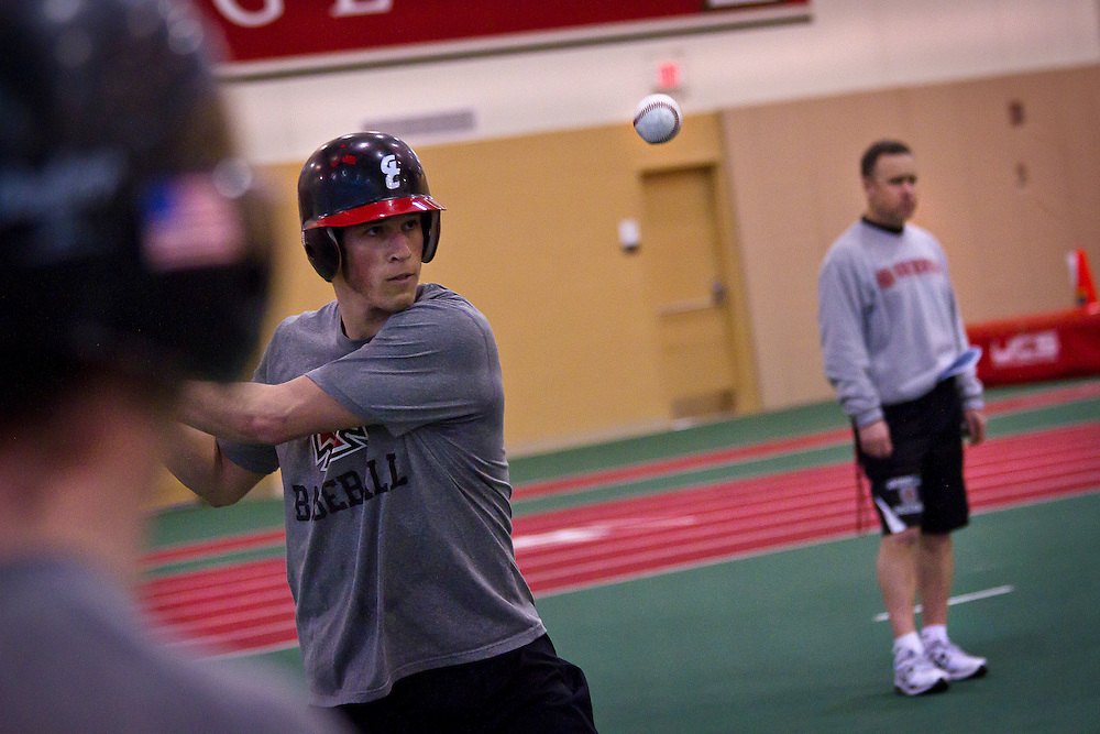 T.J. Goetz '14 focuses hard on hitting a ground ball during indoor practice in the Bear Fieldhouse Wednesday night as head coach Tim Hollibaugh, right, looks on.