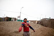 A boy plays with a deflated ball on Friday, Apr. 17, 2009 in Ventanilla, Peru.