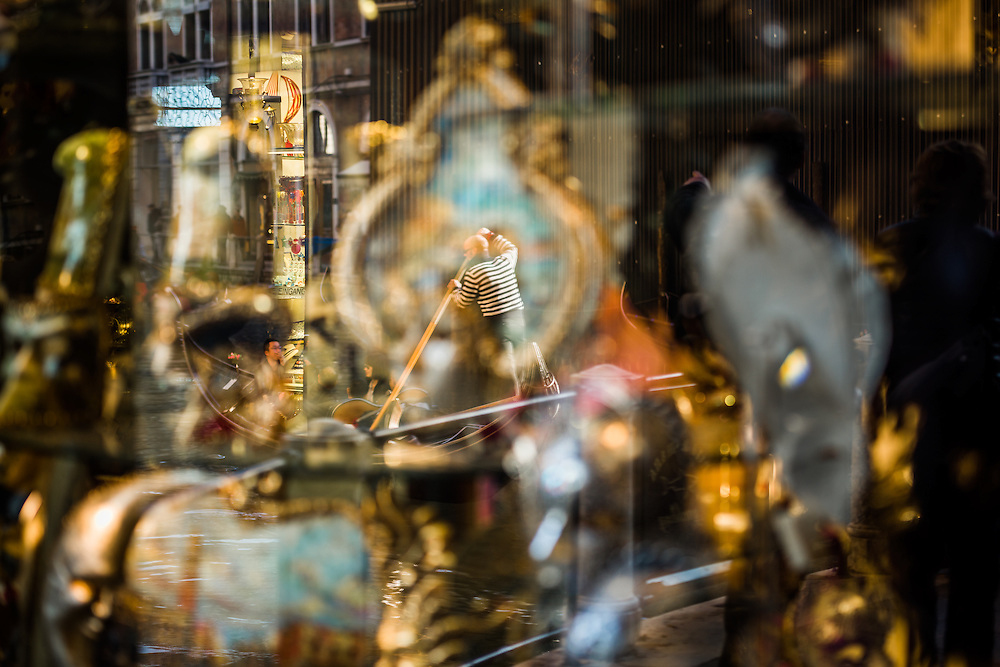 a gondolier is seen rowing along the canal in the reflection of a shop window where carnival masks are for sale