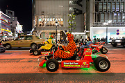 Western and Asian tourists enjoy riding go carts  on a tour organised by the Mari Car Company through Shibuya crossing, dressed at characters from the  Super Mario Carts game and Tigger from Winnie the Pooh. Shibuya, Tokyo, Japan Friday April 20th 2018.The carts that trade on the Super Mario Carts game idea and charters are a popular tourist attraction in Tokyo. Though there are safety and copyright issues that may soon force the company to stop running the tours