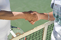 Tennis players shaking hands over net