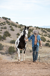 cowboy walking with a horse on a ranch