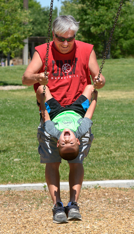 gbs060517a/ASEC -- Leo Martinez of Albuquerque swings in tandem with his grandson, Xavier Crispen, 6, in Tiquex Park on Monday, June 5, 2017. Martinez said he babysits Xavier and his granddaughter, Makayla Crispen, 9, three days a week during the summer. (Greg Sorber/Albuquerque Journal)