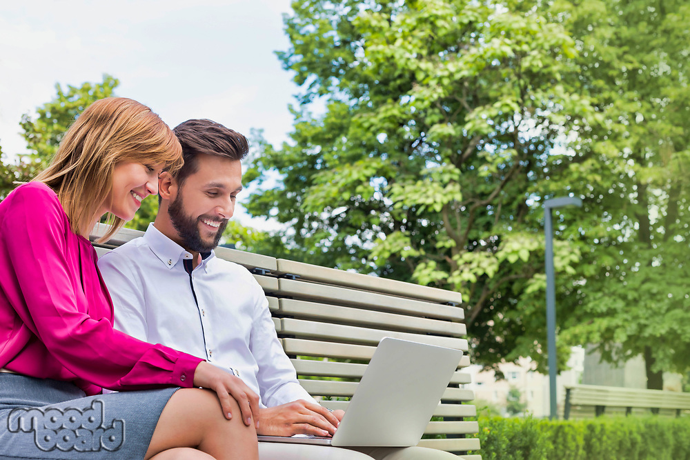 Portrait of businessman and businesswoman sitting on bench while working on laptop