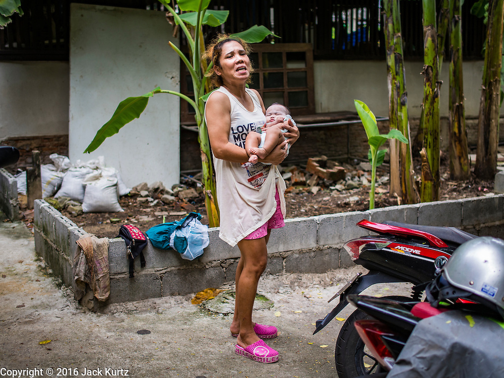 13 AUGUST 2016 - BANGKOK, THAILAND: A woman carries her newborn infant through the Pom Mahakan slum in Bangkok. Residents of the slum have been told they must leave the fort and that their community will be torn down. The community is known for fireworks, fighting cocks and bird cages. Mahakan Fort was built in 1783 during the reign of Siamese King Rama I. It was one of 14 fortresses designed to protect Bangkok from foreign invaders. Only of two are remaining, the others have been torn down. A community developed in the fort when people started building houses and moving into it during the reign of King Rama V (1868-1910). The land was expropriated by Bangkok city government in 1992, but the people living in the fort refused to move. In 2004 courts ruled against the residents and said the city could take the land. Eviction notices have been posted in the community but most residents have refused to move. Residents think Bangkok city officials will start evictions around August 15, but there has not been any official word from the city.      PHOTO BY JACK KURTZ