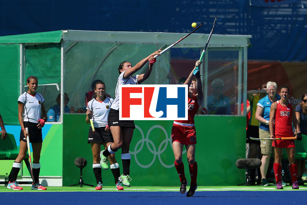 RIO DE JANEIRO, BRAZIL - AUGUST 15:  Charlotte Stapenhorst #12 of Germany and Julia Reinprecht #12 of United States reach for a high pass during the quarter final hockey game on Day 10 of the Rio 2016 Olympic Games at the Olympic Hockey Centre on August 15, 2016 in Rio de Janeiro, Brazil.  (Photo by Christian Petersen/Getty Images)