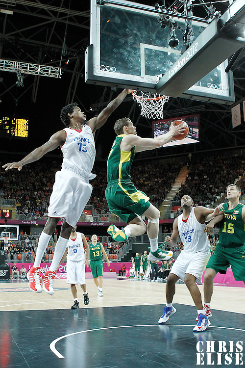 02 August 2012: Lithuania Martynas Pocius goes for the reverse layup past Mickael Gelabale during 82-74 Team France victory over Team Lithuania, during the men's basketball preliminary, at the Basketball Arena, in London, Great Britain.