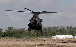 12 june 2010. Wetlands of Plaquemines Parish, South Louisiana. <br /> An army chinook CH-47 twin rotor helicopter on a sandbagging mission. Sand bags attempt to join the dots and connect what little remains of fragile barrier islands. It is unlikely the bags will survive a hurricane. Where once there was land, there is only the mere outline of old canals and channels, many dug by oil companies to pump their product ashore with little regard to the effects the chopping up of the wetlands would have. Chronic erosion of the land, a football pitch every 50 minutes, greatly reduced protection from hurricanes and inpending BP oil slicks is the direct result of mismanagement and utter disregard for the environment. The army corps of engineers and the oil companies, together with inept government have a great deal to answer for. <br /> View from a blackhawk helicopter flown by airmen of the Nebraska Air National Guard over southern Louisiana as they assist in the dumping of sand bags onto barrier islands in a vain attempt to prevent BP oil from getting into the inner  wetlands. As valient as their efforts are, the dumping of sand bags may well prove to be a complete waste of manpower, resources and money. A hurricane will likely roll over and blast through any sandbag 'barrier island,' blowing thousands of large white plastic bags far and wide across the landscape. That will really help the environment! <br /> Meanwhile, the mighty Mississippi river runs straight out to sea nearby, her valuable land building sediment carried far out into deep ocean as the region struggles to find a way to reverse the disasterous effects of man's inteference with her flow. <br /> Photo credit; Charlie Varley.